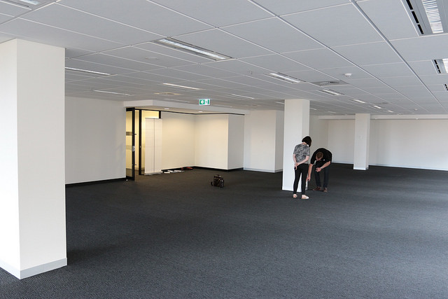 An empty office space - white walls; grey carpet.