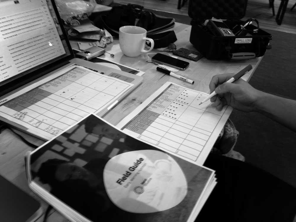 photo showing person organising recruiting with a list, guide, and their laptop computer