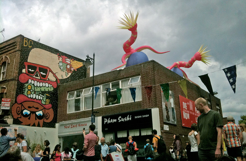 Street fair in London. Lots of people walking around, banners, street art.